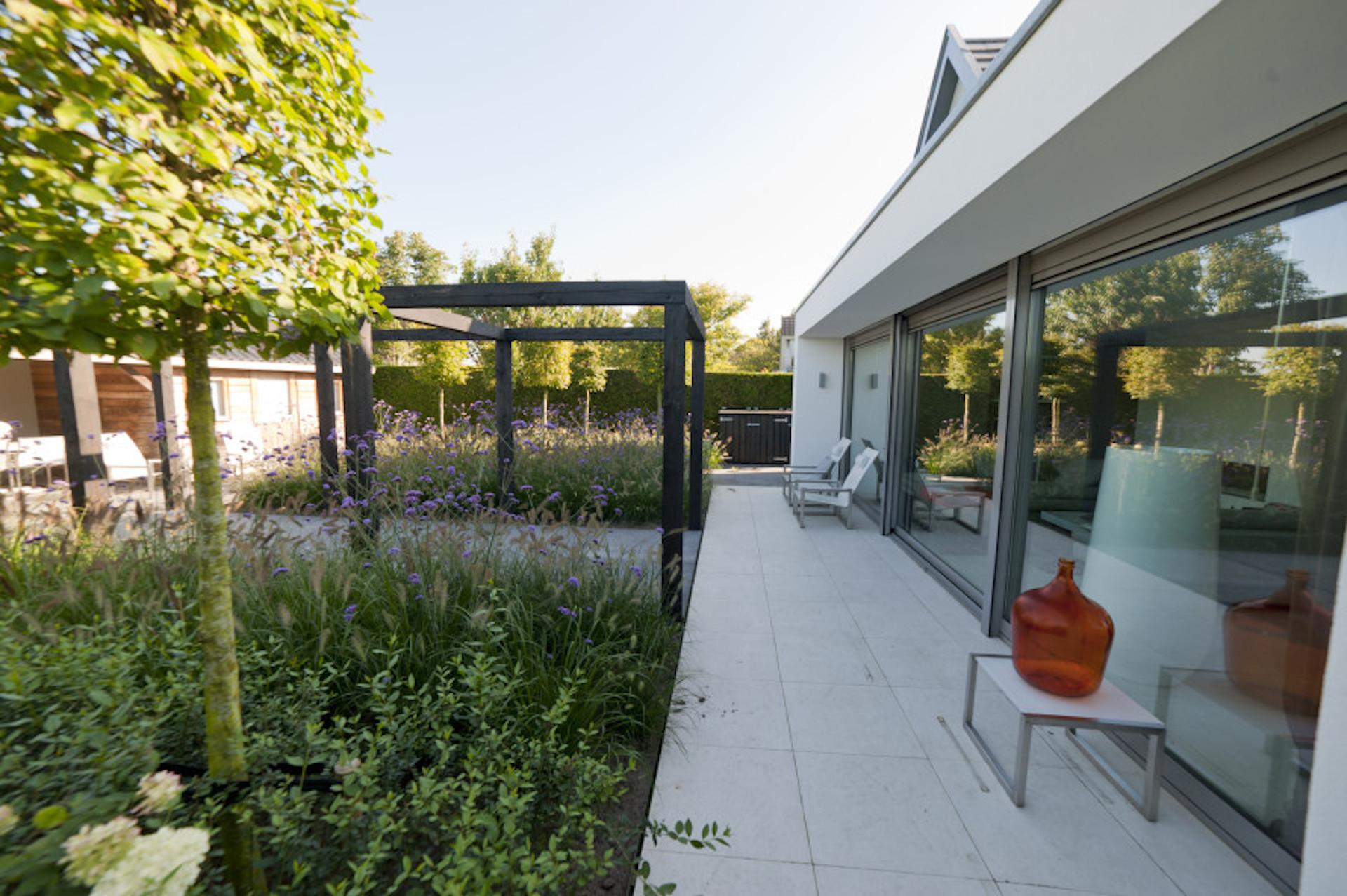Tuinontwerp Outlook Groenprojecten strak vormgegeven tuin met Stoere pergola zwart - Outlook Groenprojecten